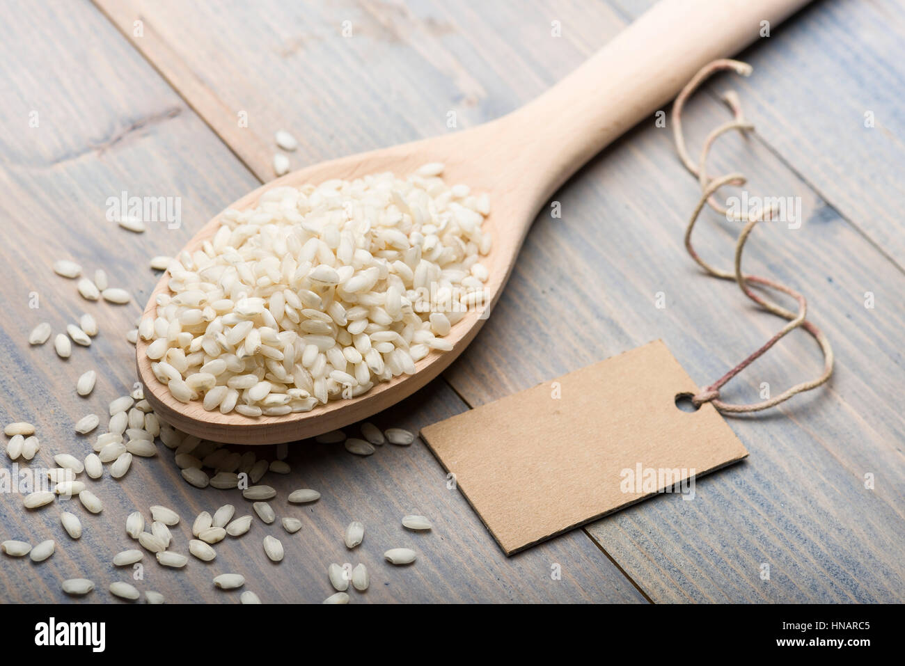 heap of white rice in wooden spoon on table with label for text. - Stock Image