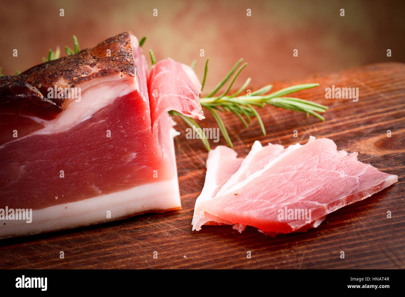 italian speck prosciutto on wooden chopping board - italian food - Stock Image