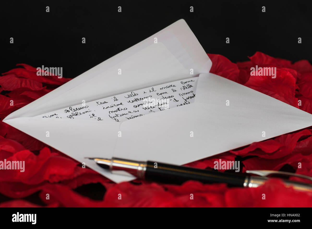 love letter on red rose petals and black background - Stock Image