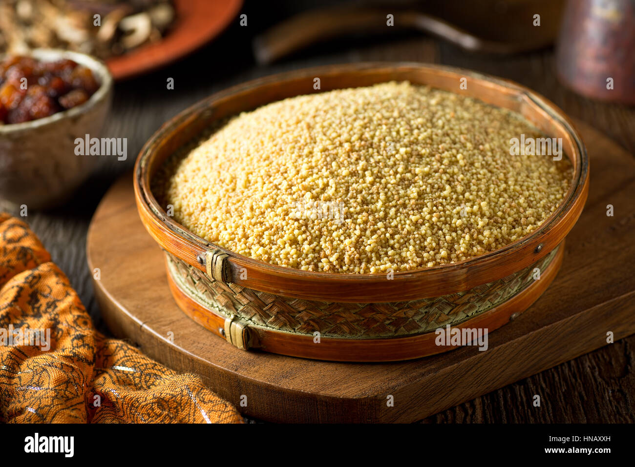 A bowl of raw organic couscous. - Stock Image