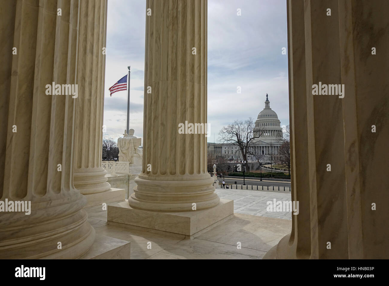 From portico of U.S. Supreme Court Building, view Capitol Building, home of the US Congress.  Flag flying. Washington, - Stock Image
