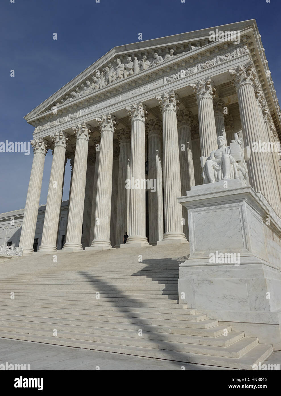 U.S. Supreme Court Building low angle.  Authority of Law statue; flag shadow on steps. - Stock Image