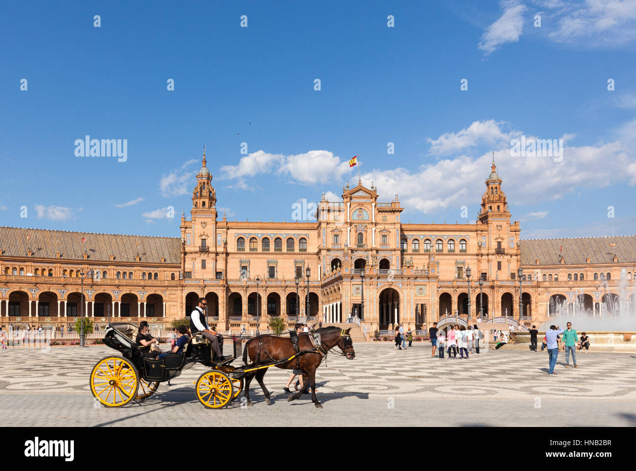 Seville, Spain - April 30, 2016: A sunny day at Plaza de Espana, tourists visiting the famous square, a horse-drawn - Stock Image