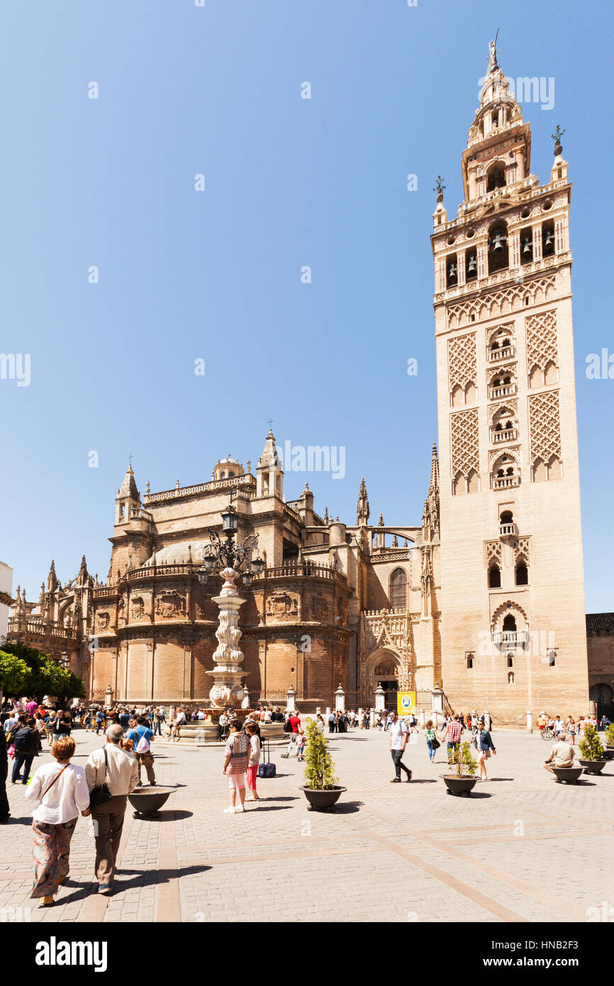 Seville, Spain - May 1, 2016: The Giralda, former minaret, today bell tower of Seville Cathedral. Tourists around - Stock Image