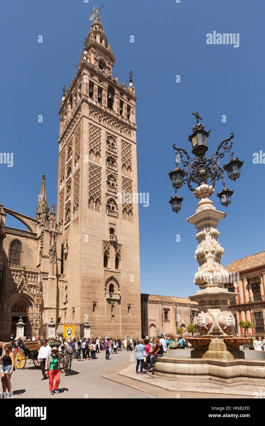 Seville, Spain - May 1, 2016: La Giralda, the bell tower of Seville Cathedral and the fountain on Plaza de Triunfo. - Stock Image