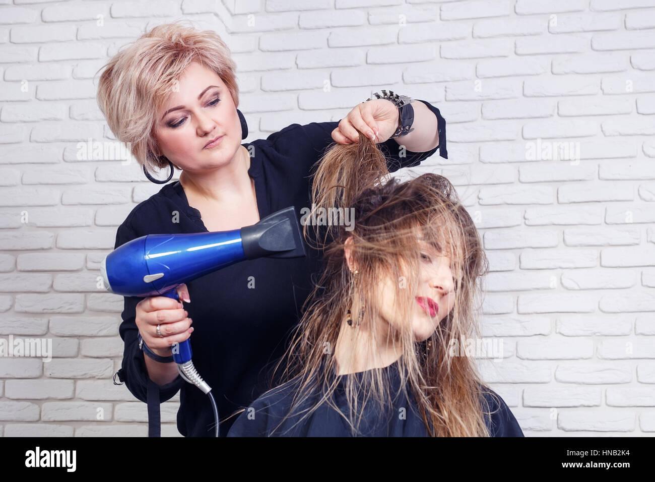 hairdresser drying hair - Stock Image
