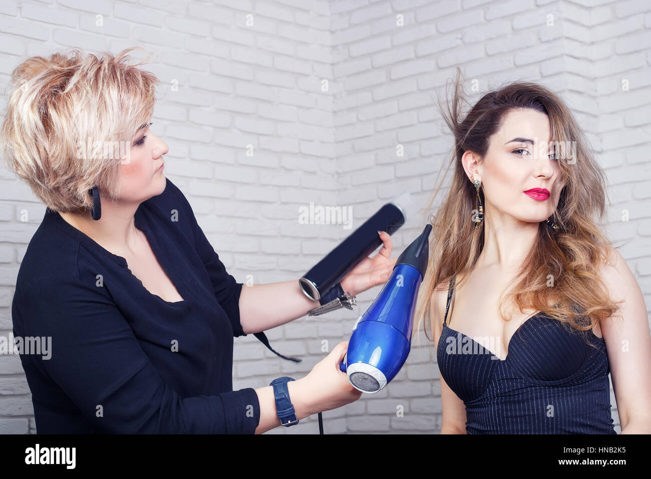 Hairdresser with hair dryer  - Stock Image