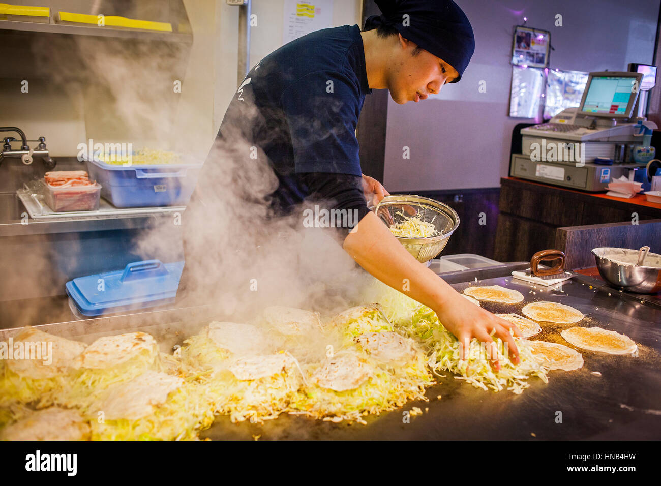 Chef Cooking Okonomiyaki,  in a restaurant of Okonomi-mura, Hiroshima, Japan Stock Photo