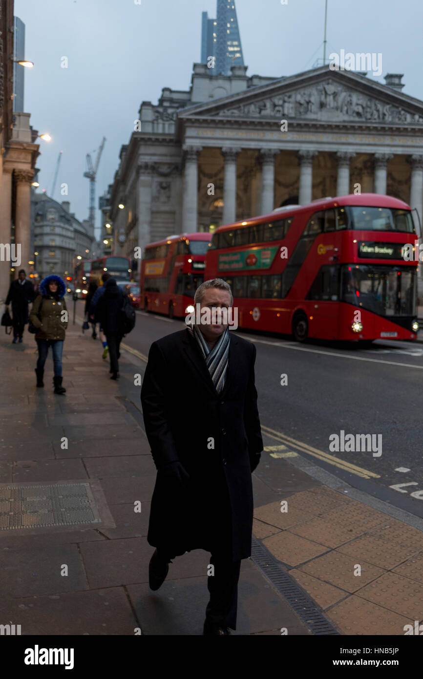 A worried-looking commuter walks past the neo-Roman pillars of Royal Exchange and buses on 9th February 2017, in - Stock Image