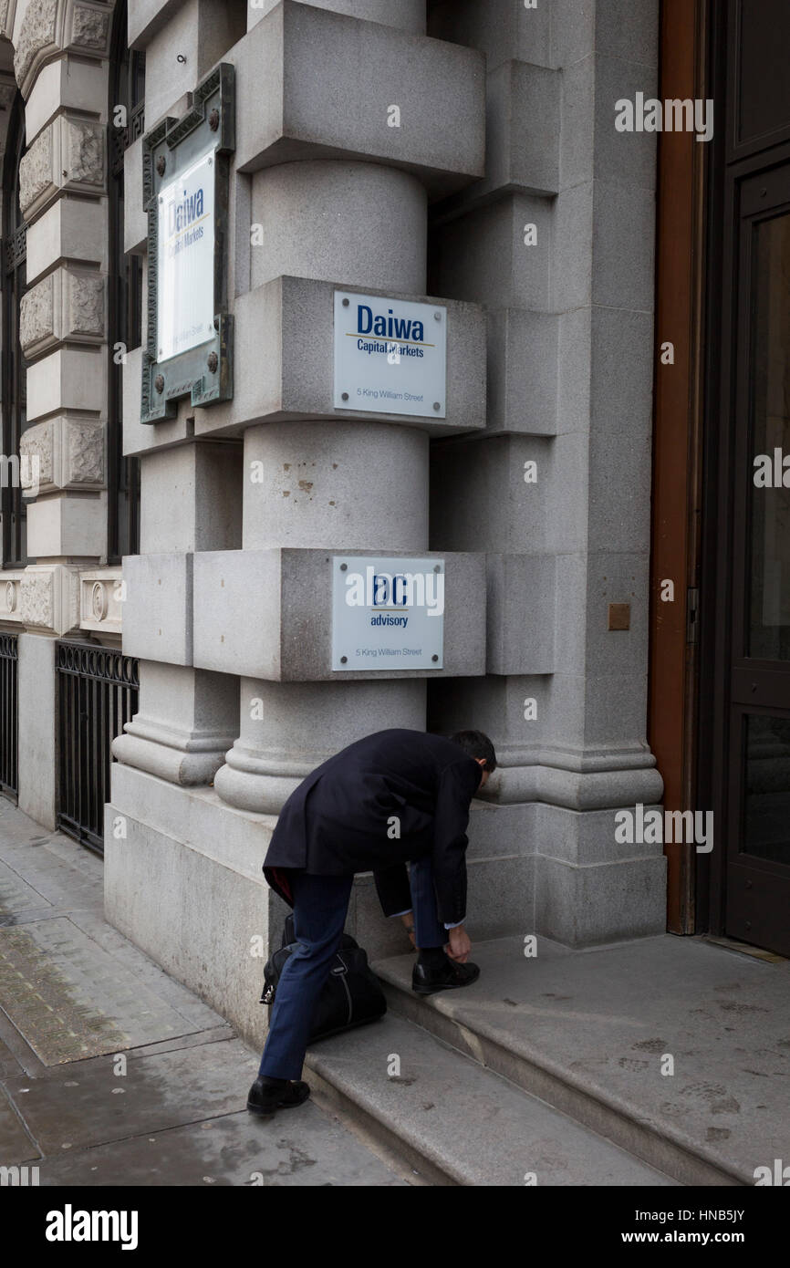 A businessman stops to tie a shoelace in the doorway of banking and financial companies, on 2nd February 2017, in - Stock Image