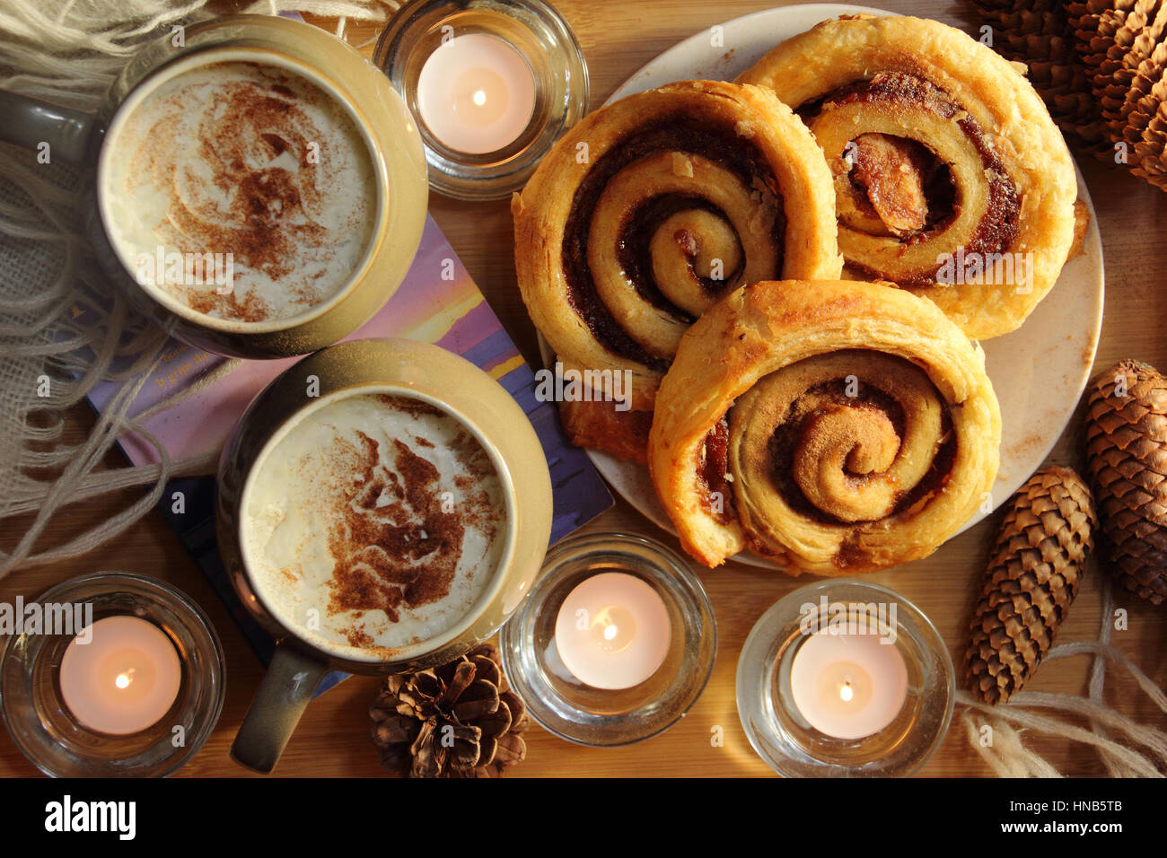 Cream topped coffee and cinnamon swirl pastries served by cosy candle light in an English home at winter - Stock Image
