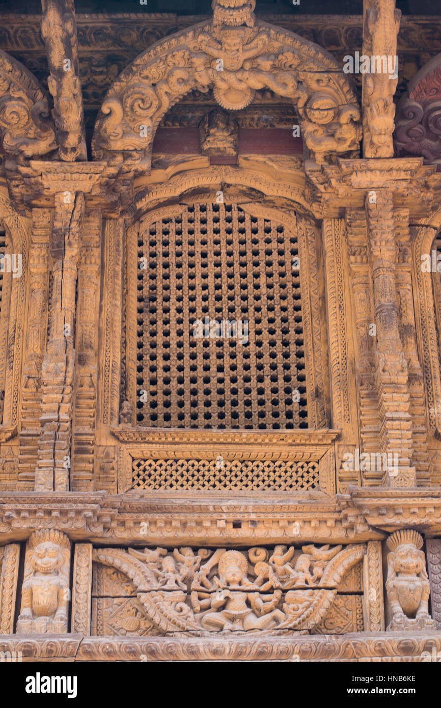 Lattice work window topped by a carved wooden arch decorated with mythical animal figures in a temple in Kathmandu, - Stock Image