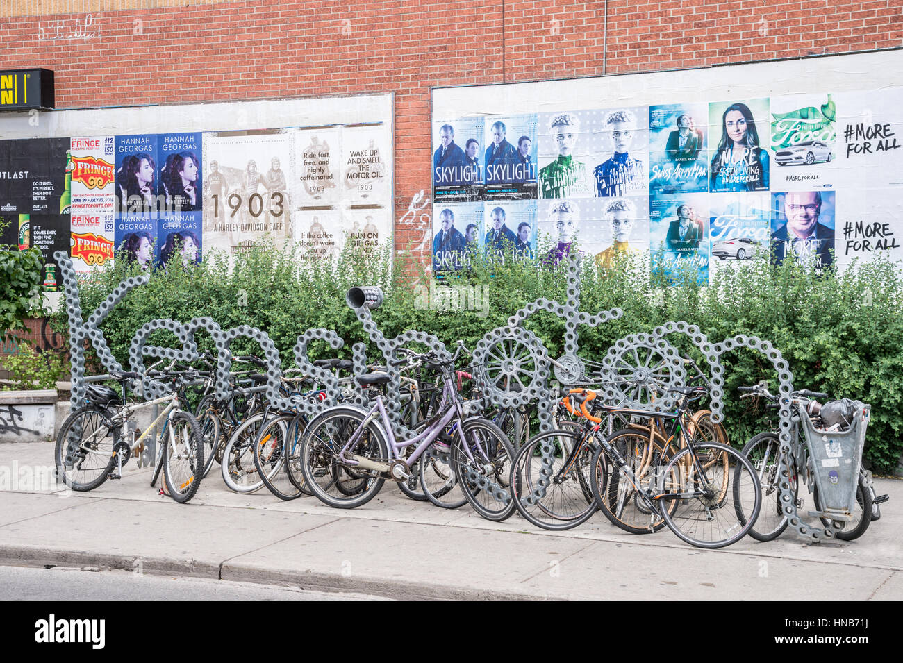 Toronto, Canada - 2 July 2016: Bike racks and Kensington neighbourhood metal sign in Toronto, Canada. - Stock Image