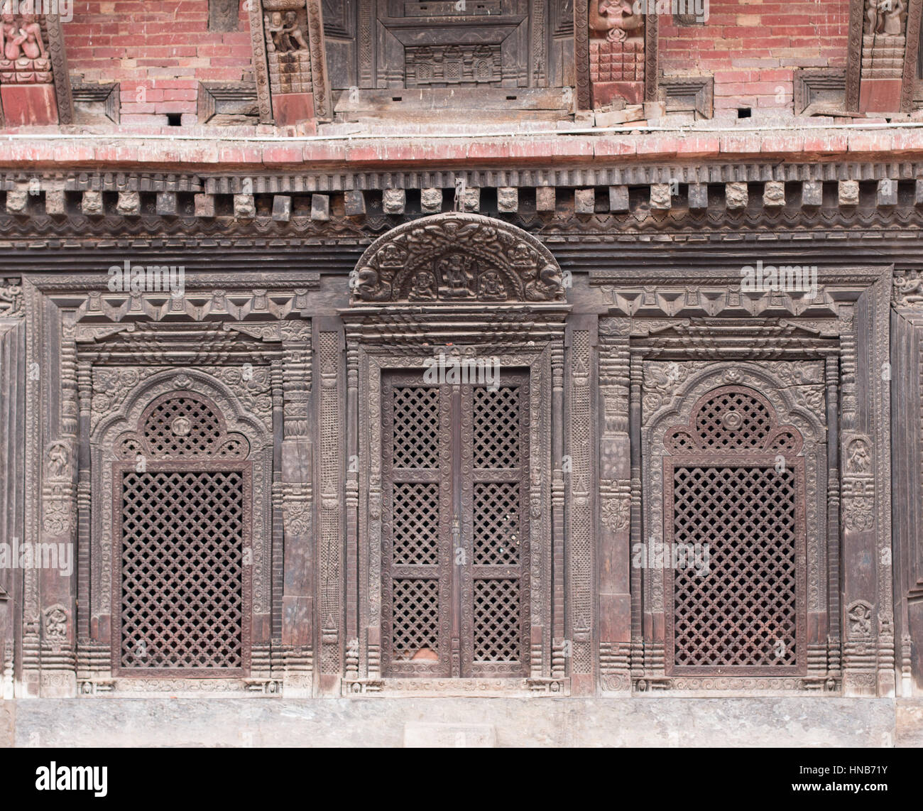 Intricate wooden lattic-work windows and doors of an old building in Bhaktapur, Kathmandu, carved in the traditional - Stock Image