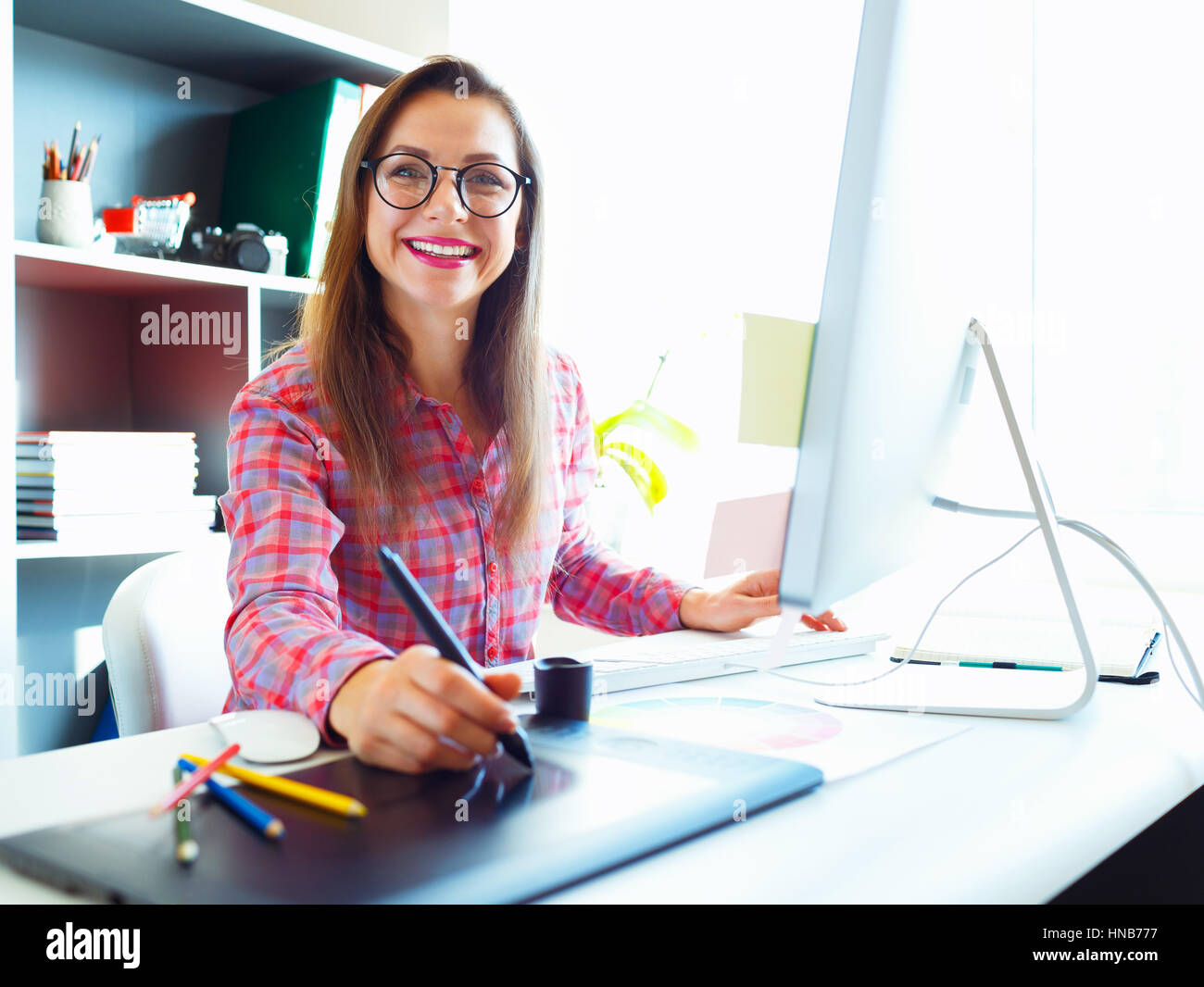 Graphic designer drawing something on graphic tablet at the home office - Stock Image
