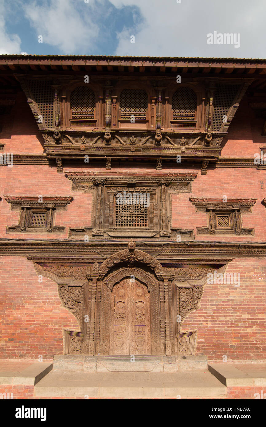 Exterior an old brick building in Bhaktapur, Kathmandu, adorned with a richly carved door and window in the traditional - Stock Image