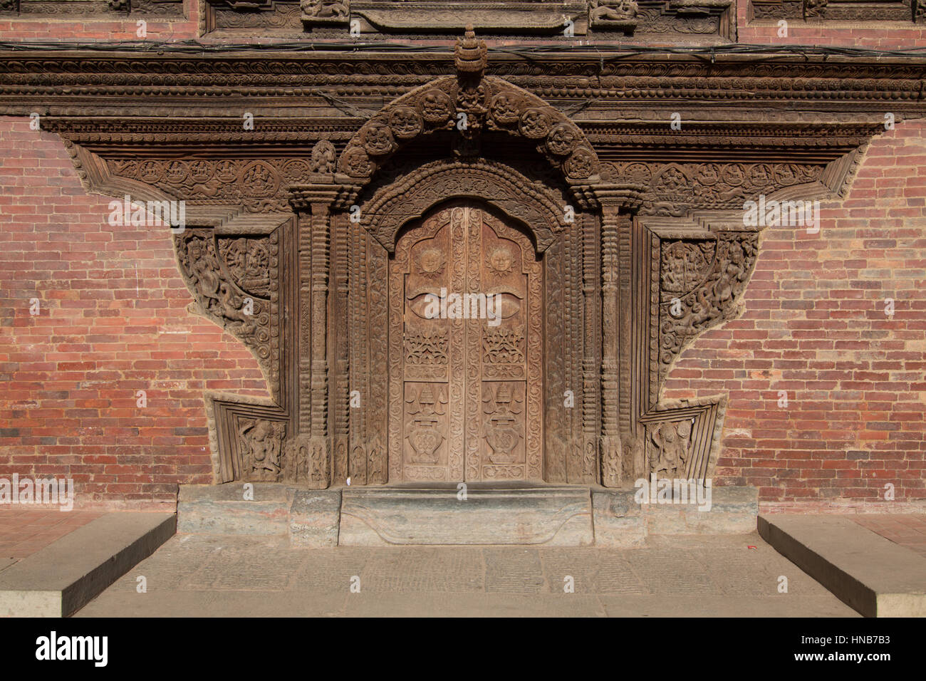 A richly carved wooden door adorned with figures of Hindu gods and celestial creatures on a brick building in Bhaktapur, - Stock Image