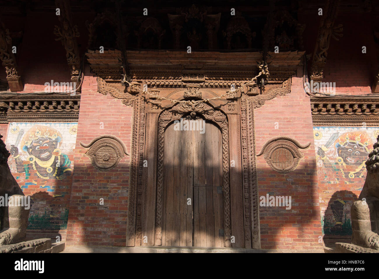 Intricately carved wooden door and lintel of an old building in Bhaktapur, Kathmandu with religious motifs - Stock Image