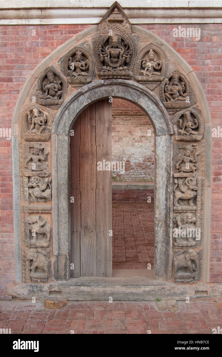 Arched wooden doorway adorned with intricate carvings of Hindu gods and goddesses in Bhaktapur, Kathmandu. This - Stock Image