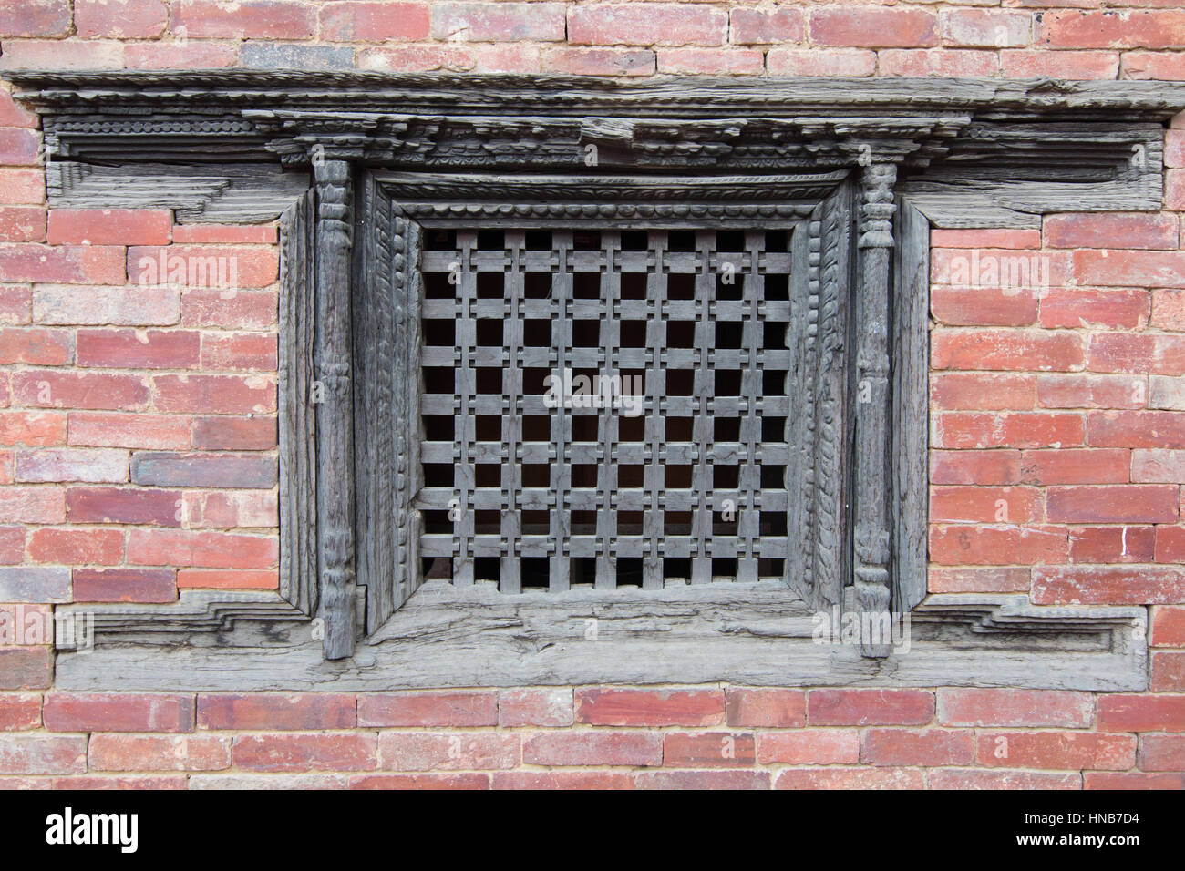 Delicate traditional wooden lattice-work window on a brick building in Bhaktapur, Kathmandu - Stock Image