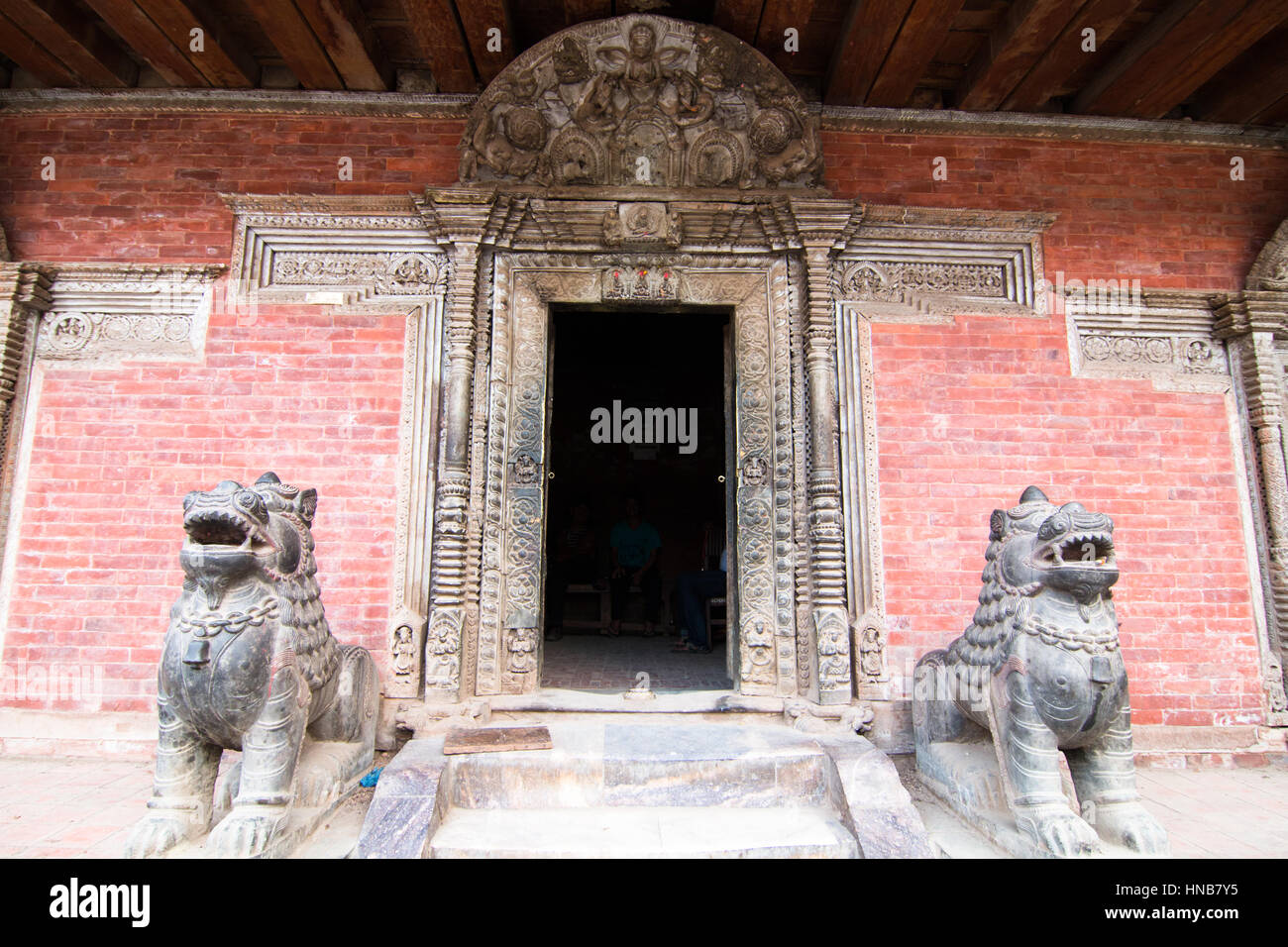 Lions guard the doorway at the entrance of an old building with an intricately carved wooden lintel in Bhaktapur, - Stock Image