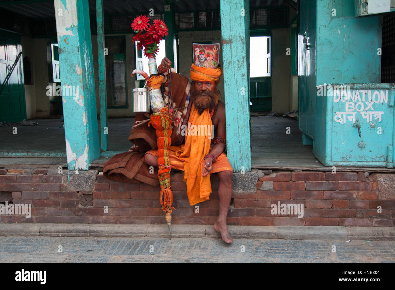 Sadhu in saffron robes at the Swayambhunath pagoda, Kathmandu, Nepal who claims to be from the holy city of Varanasi - Stock Image