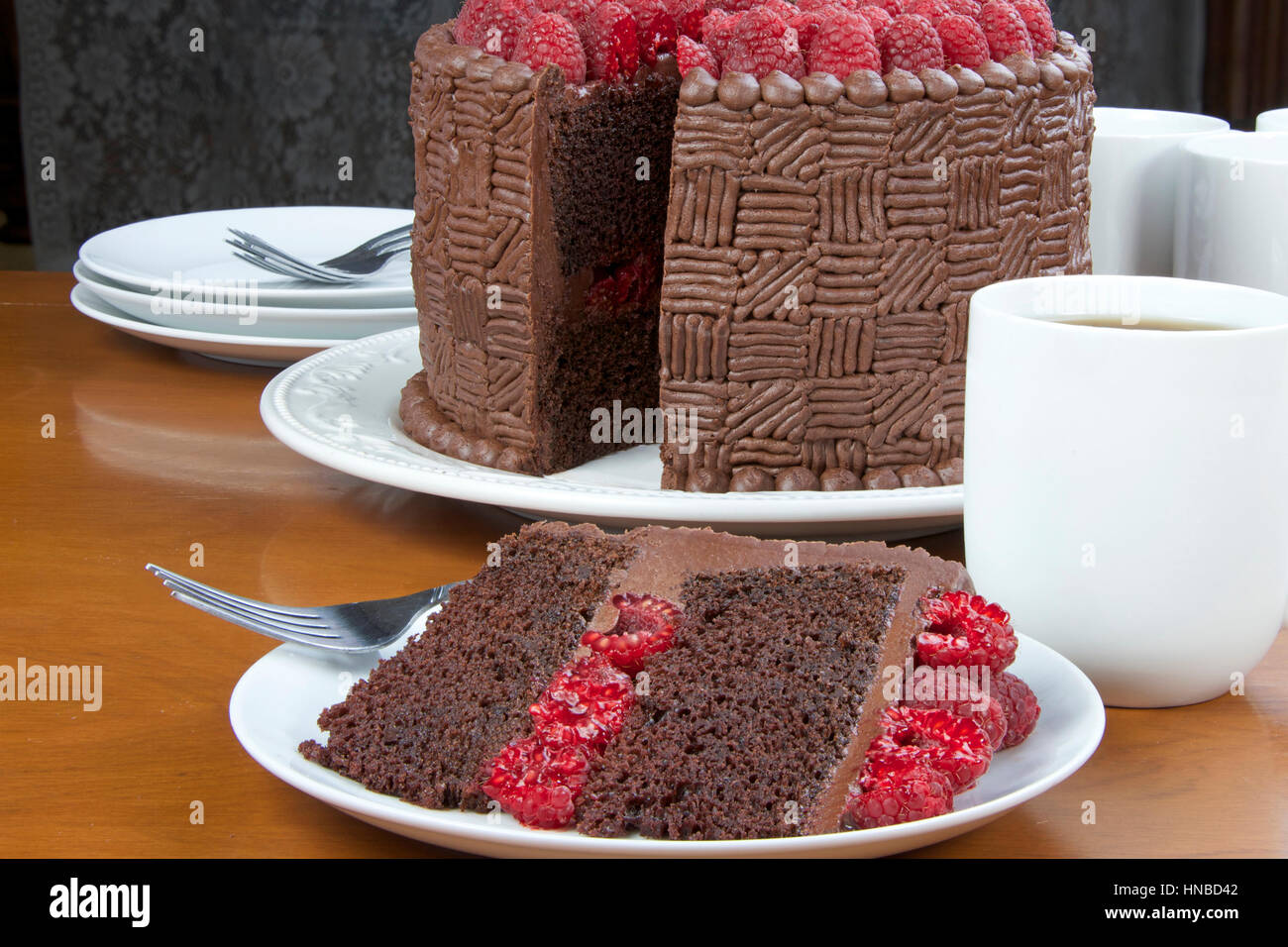 Slice of Home made original design chocolate cake with fresh raspberry filling and raspberries on top served on a plate with whole cake in the backgro & Slice of Home made original design chocolate cake with fresh Stock ...