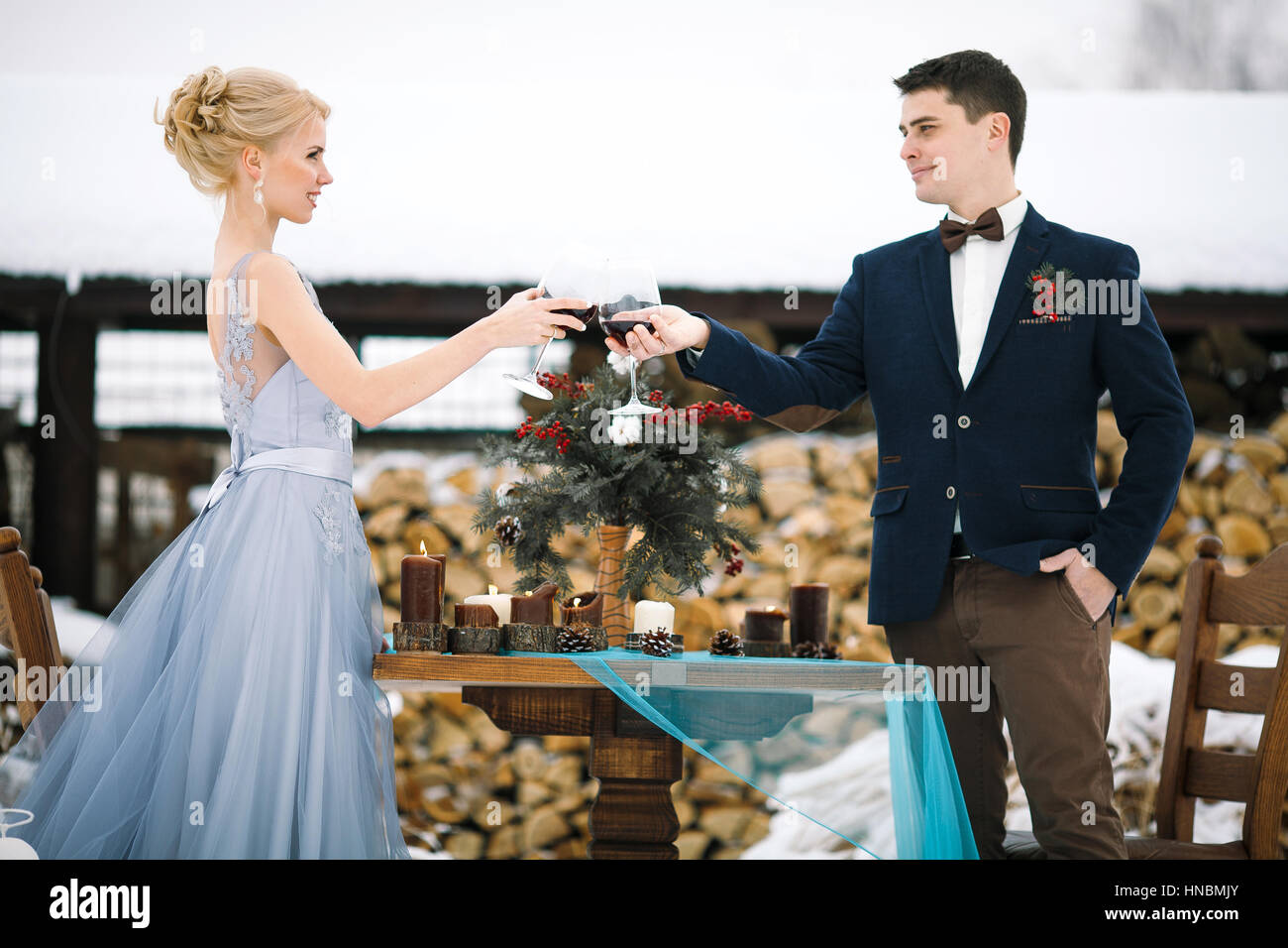 Winter wedding outdoor on firewood background. Bride and groom stand near table and clink glasses with wine. Beside - Stock Image