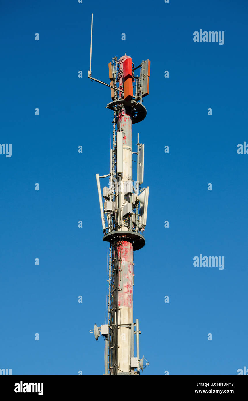 Mobile antenna on blue sky background - Stock Image