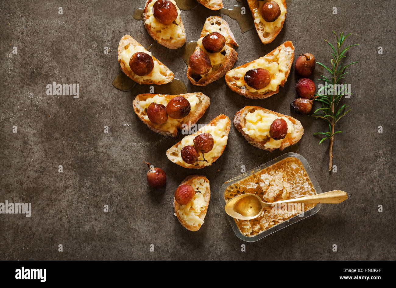 hors doeuvres with baked camembert, grapes and honey on grey stone background - Stock Image