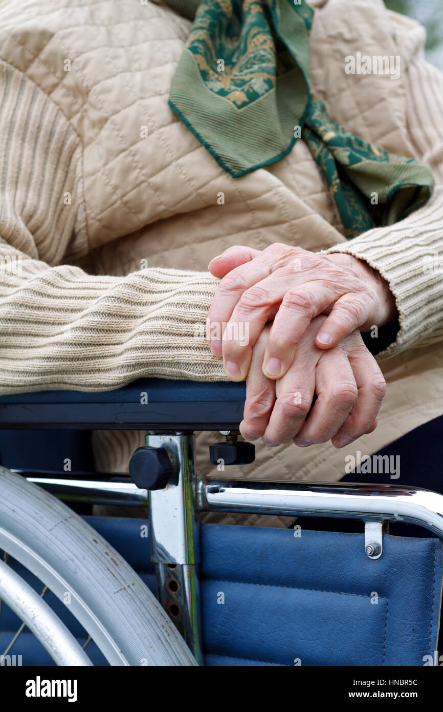 Handicapped elderly woman sitting in a wheelchair outdoor - Stock Image