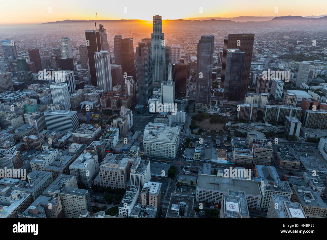 Los Angeles, California, USA - July 21, 2016:  Urban aerial of sun setting behind the US Bank Tower in downtown Stock Photo