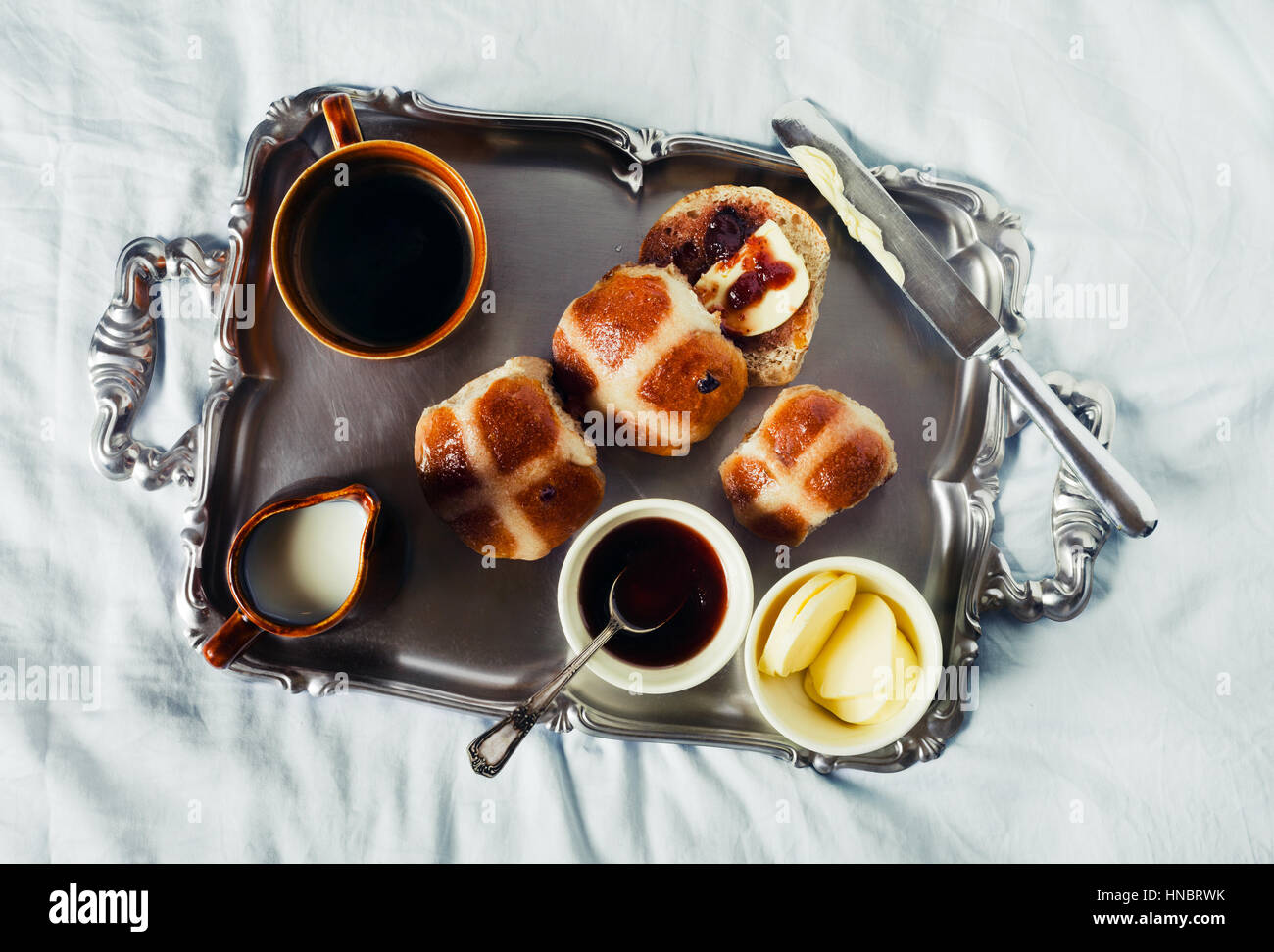 Breakfast on a silver tray on blue sheets on the bed. Scones with Jam and butter, and hot strong Coffee with milk. - Stock Image