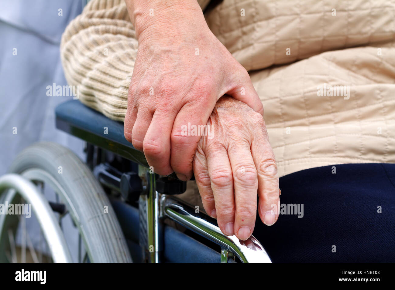 Elderly handicapped woman sitting in a wheelchair - Stock Image