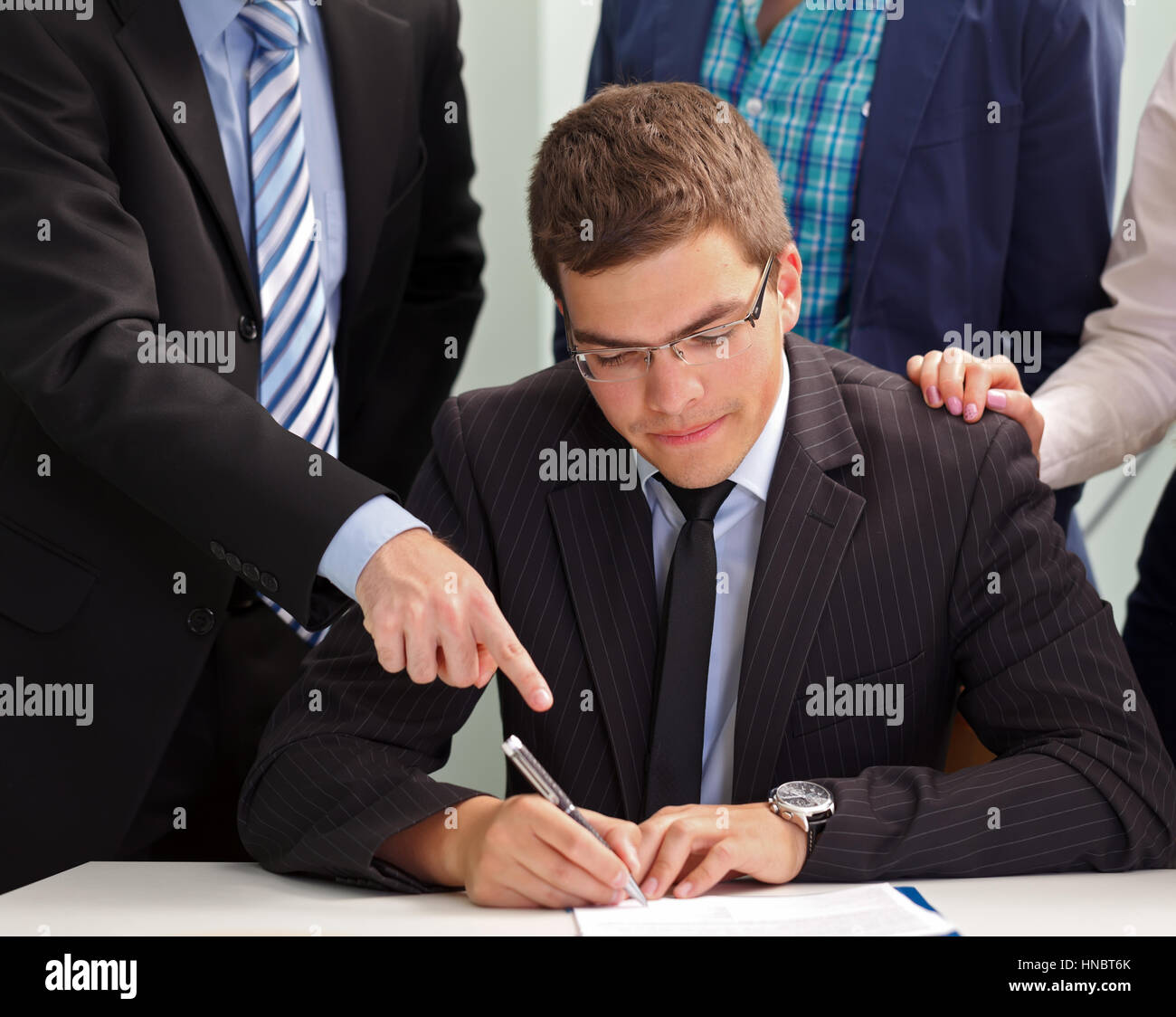 Confident businessman signing the contract in front of his team - Stock Image