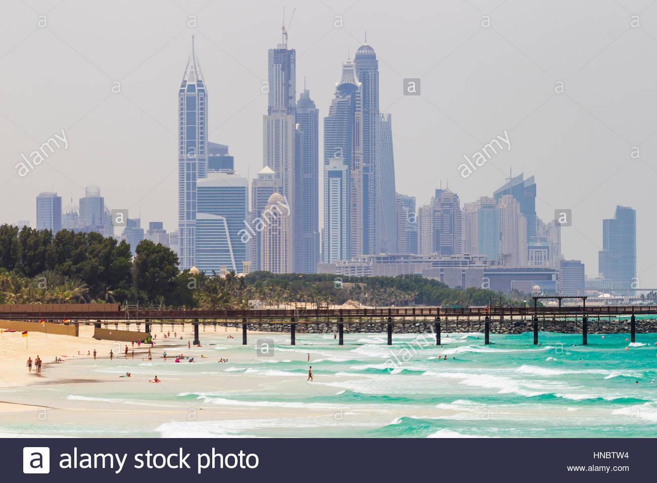 Waves coming ashore on Persian Gulf beaches, with a backdrop of the Dubai skyline, in 2014. - Stock Image