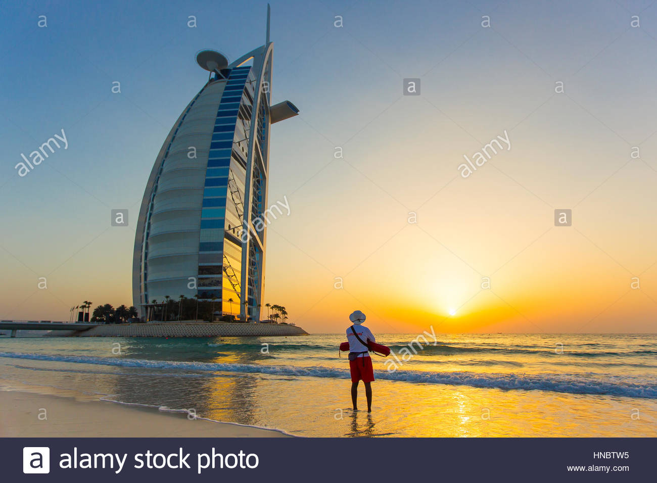 A lifeguard watching the sunset near the Burj Al Arab hotel, on the Persian Gulf. - Stock Image