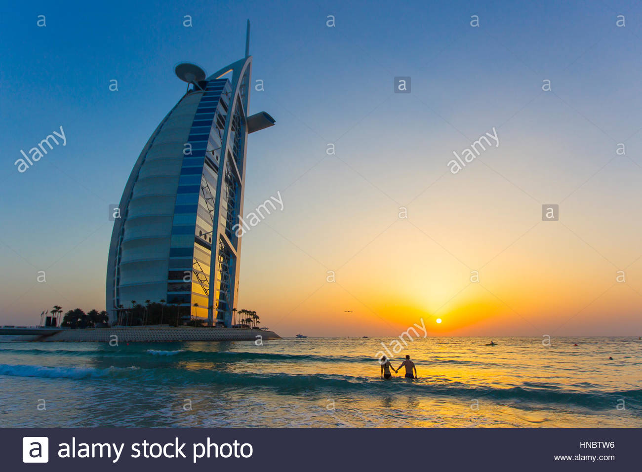 A couple holding hands and watching the sunset in the Persian Gulf, near the Burj Al Arab hotel. - Stock Image