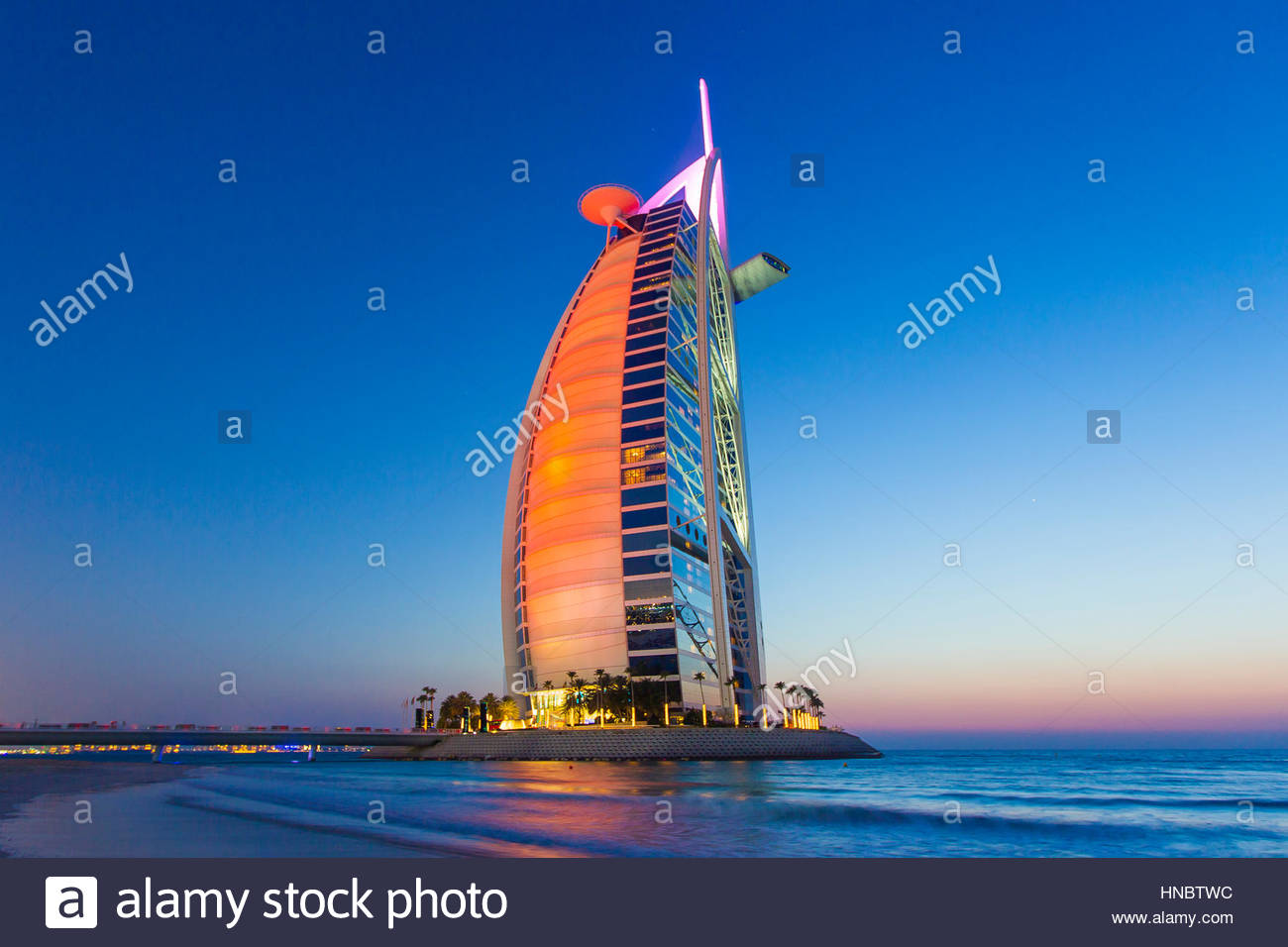 The Burj Al Arab hotel, on the Persian Gulf, ablaze in colorful reflections. - Stock Image