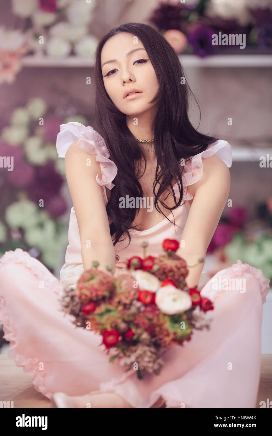 Beautiful asian woman florist in pink dress with bouquet of flowers beautiful asian woman florist in pink dress with bouquet of flowers in hands in flower store izmirmasajfo Image collections