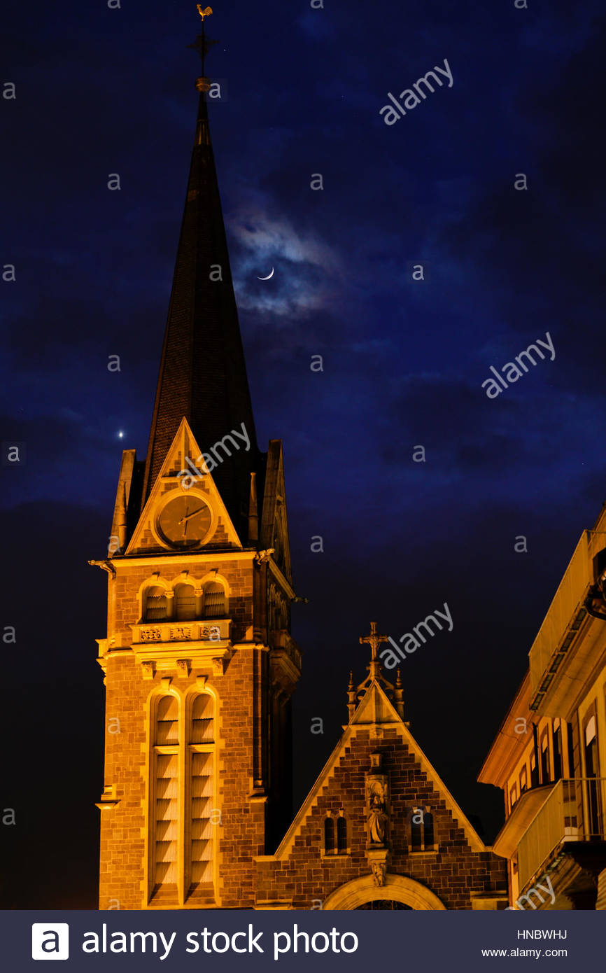 The Moon and Venus pairing in a conjunction over a church at night. - Stock Image