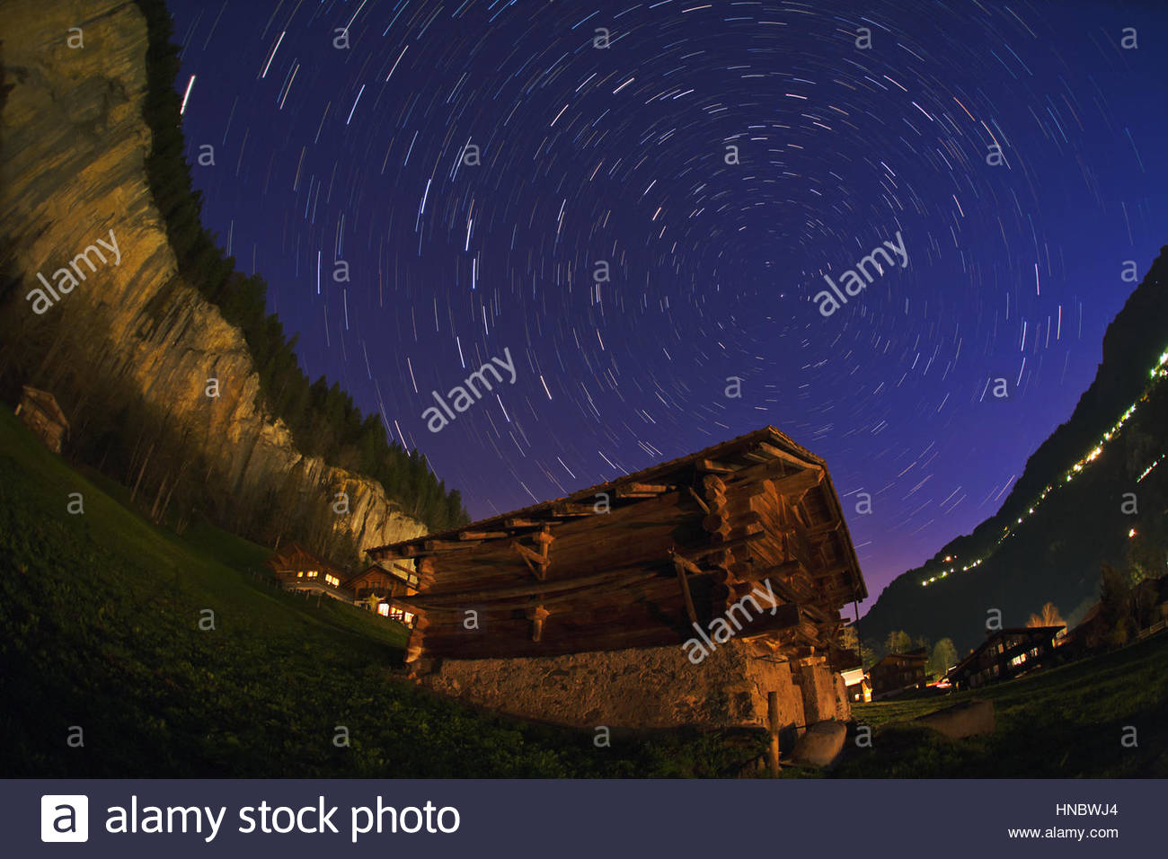 As the Earth rotates during an hour-long exposure, stars circle around the north celestial pole. - Stock Image