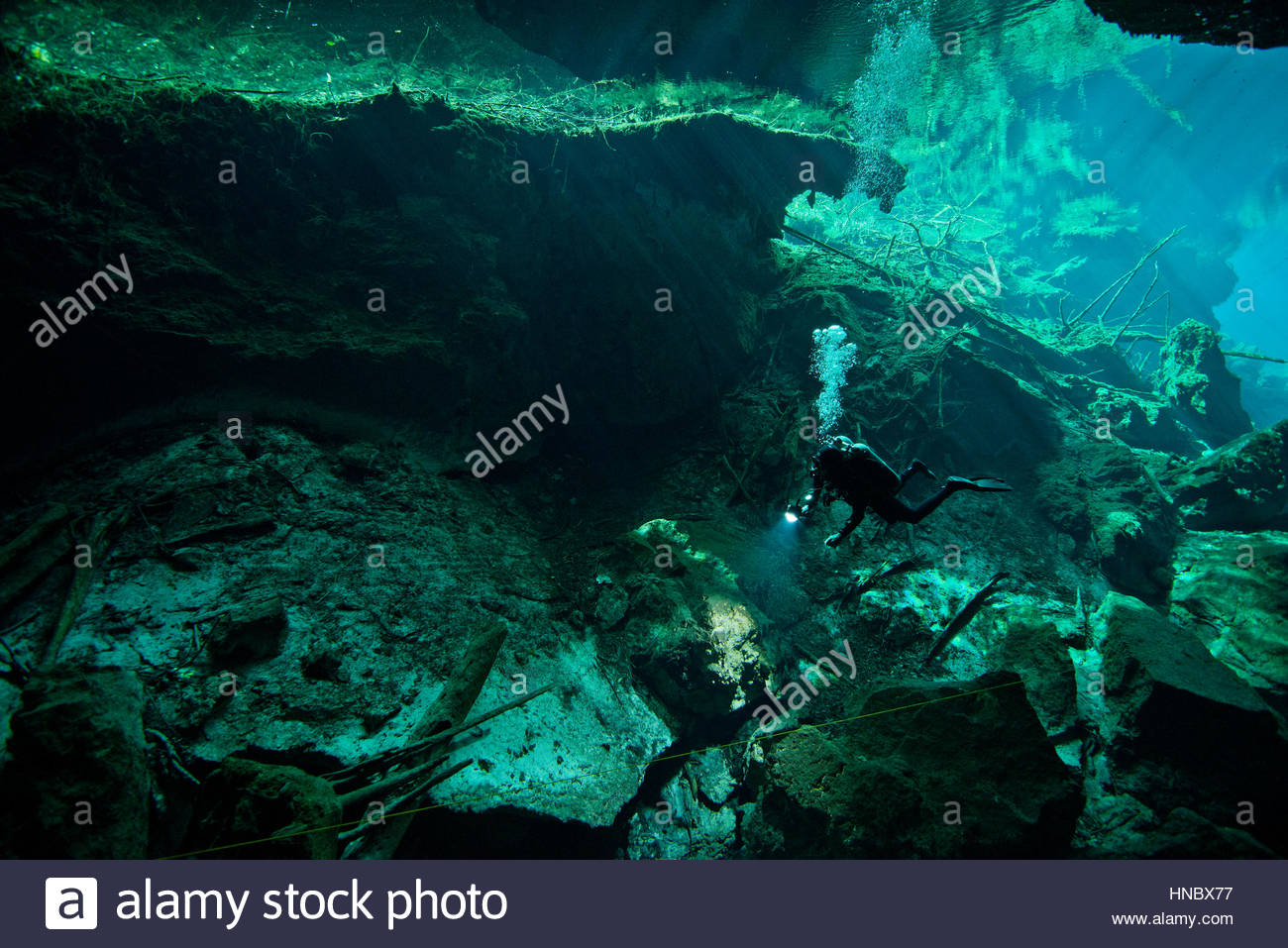 Sunlight shines on a diver exploring Cenote El Pit. - Stock Image