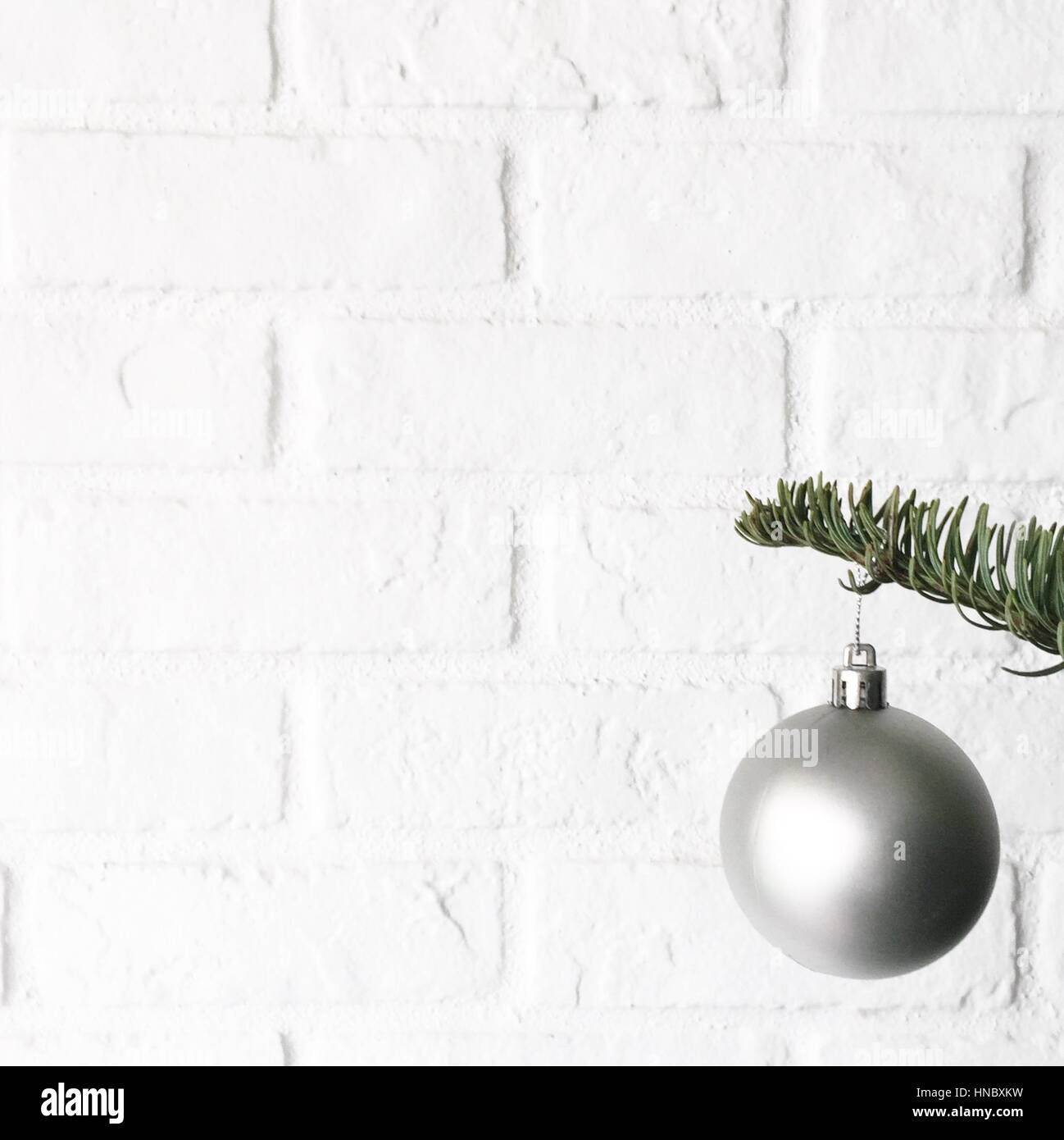 silver christmas bauble hanging on a christmas tree stock image