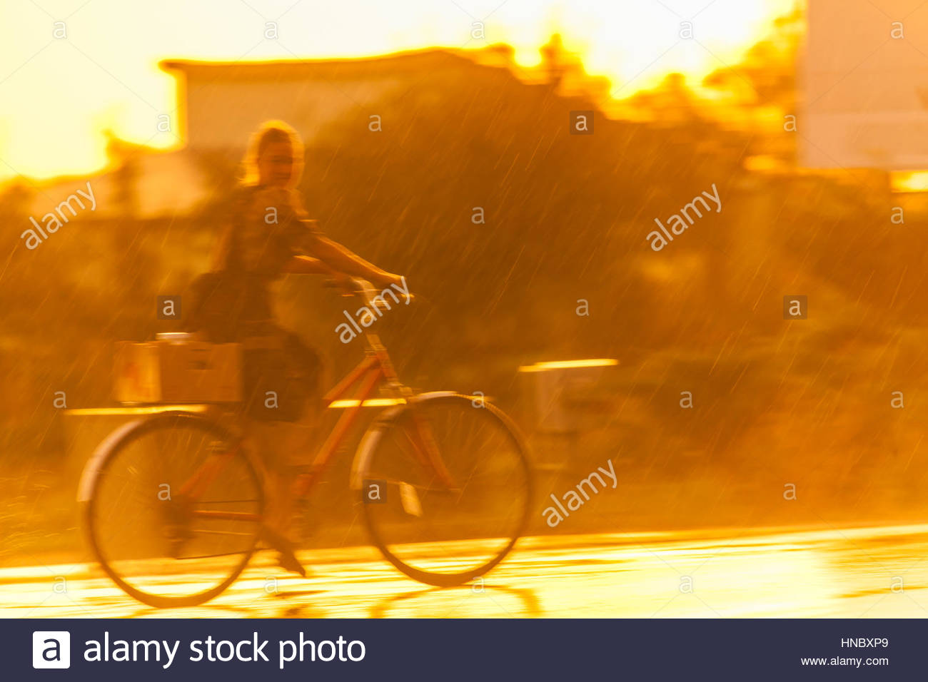 An Amish girl bikes in the rain on Route 23 near Churchtown, Pennsylvania. Stock Photo