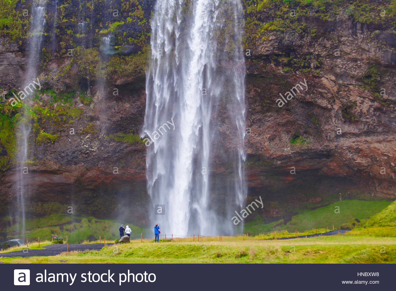 Tourists at the scenic and popular Seljalandsfoss Waterfalls. - Stock Image