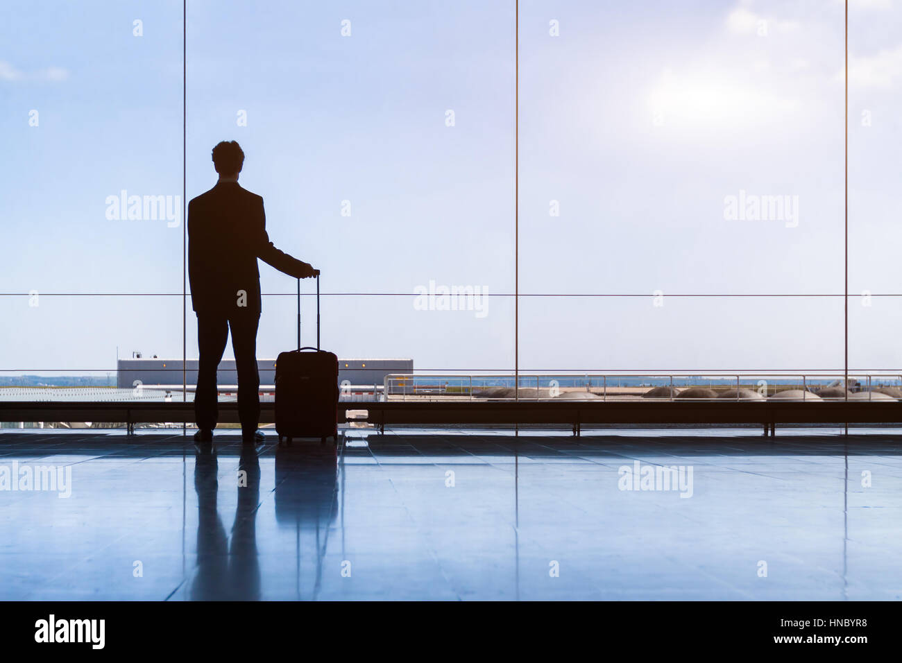 Traveler businessman in airport lounge waiting for the flight and standing with trolley luggage, business travel - Stock Image