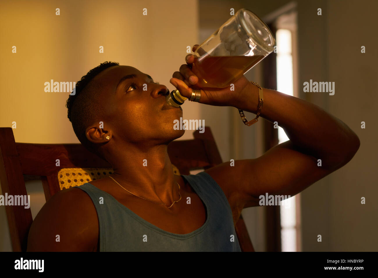 Social issues, substance abuse with alcoholic young black man drinking alchool from liquor bottle at home. - Stock Image
