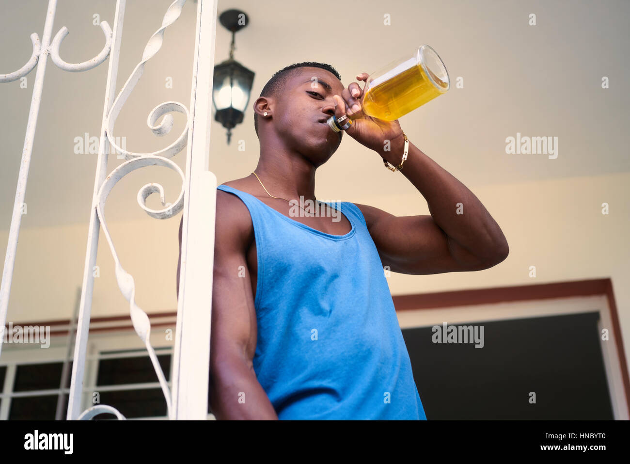 Social issues and substance abuse. Alcoholic young black man drinking alchool from liquor bottle at home, looking - Stock Image