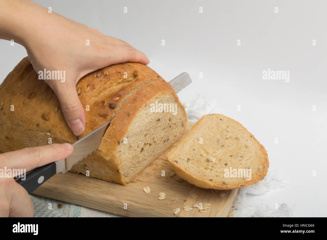 Hands Slicing Whole Wheat Bread With Bread Knife - Stock Image